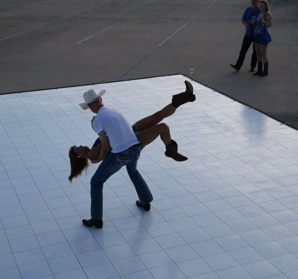 Robbin Biggersteff is lifted by Dale Litton, both of Dallas, while dancing during the Off the Rails Country Music Fest at Toyota Stadium in Frisco, Texas. They made the most of an empty dance floor in the adjacent lot outside the stadium, where food trucks and a side stage were set up. (Andy Jacobsohn/The Dallas Morning News)