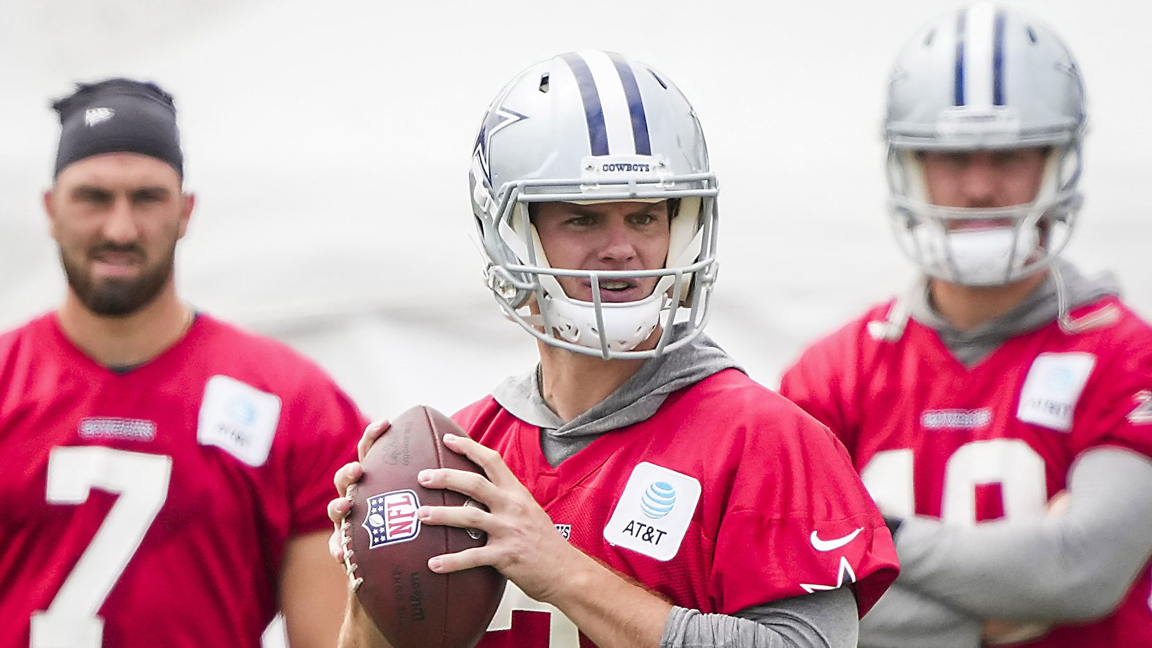 Dallas Cowboys quarterback Garrett Gilbert (3) looks to pass as quarterback Ben DiNucci (7) and quarterback Cooper Rush (10) look on during a practice at training camp on Saturday, July 24, 2021, in Oxnard, Calif.