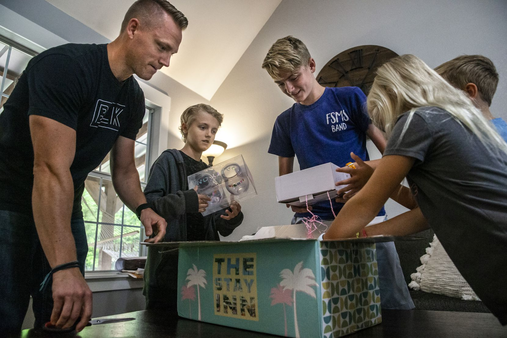 Match affinity design team lead James Walker (left) and his children Cade, 11, Boston, 14, Hudson, 9, and Avery, 7, opened a themed gift box from the company at their home in Midlothian in September.