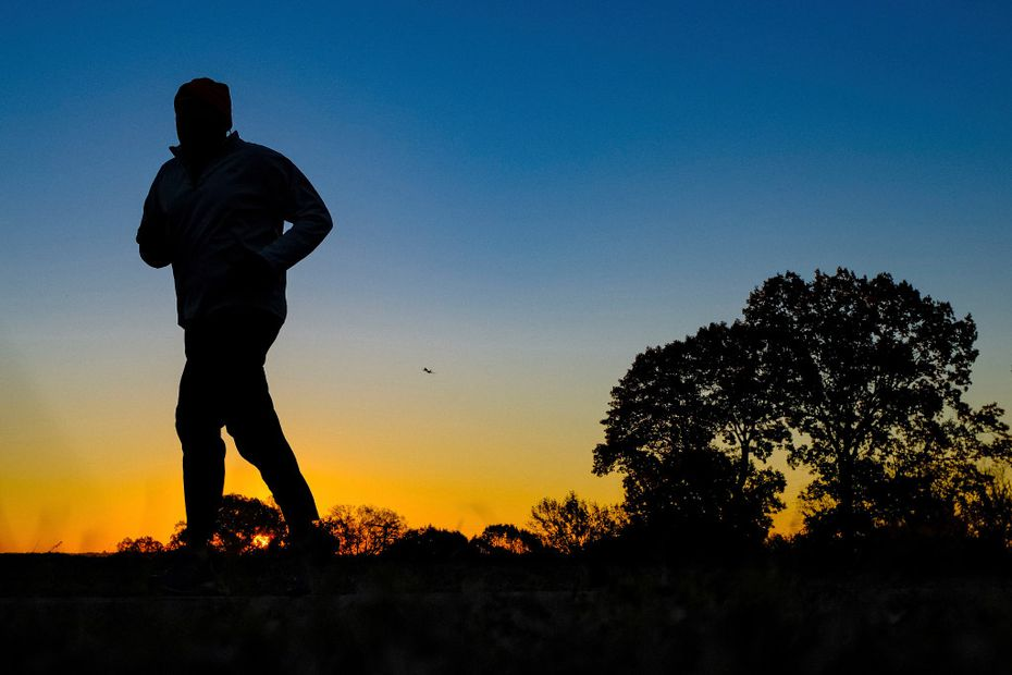 A runner is silhouetted against the sunrise on his early morning workout near Arlington National Cemetery in Arlington, Va., across the Potomac River from the nation's capital.