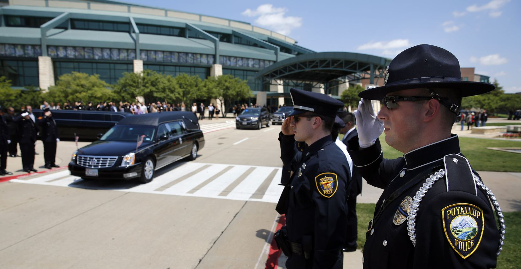 Police officers salute as the hearse passes in the funeral procession for fallen Dallas police officer Lorne Ahrens at Prestonwood Baptist Church in Plano, Wednesday, July 12, 2016. Ahrens and four other officers were gunned down during an ambush on police in downtown Dallas.