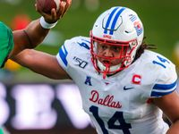 UNT quarterback Mason Fine (6) throws a pass under pressure from SMU linebacker Richard Moore (14) during the first half of an NCAA football game at Ford Stadium on Saturday, Sept. 7, 2019, in Dallas.