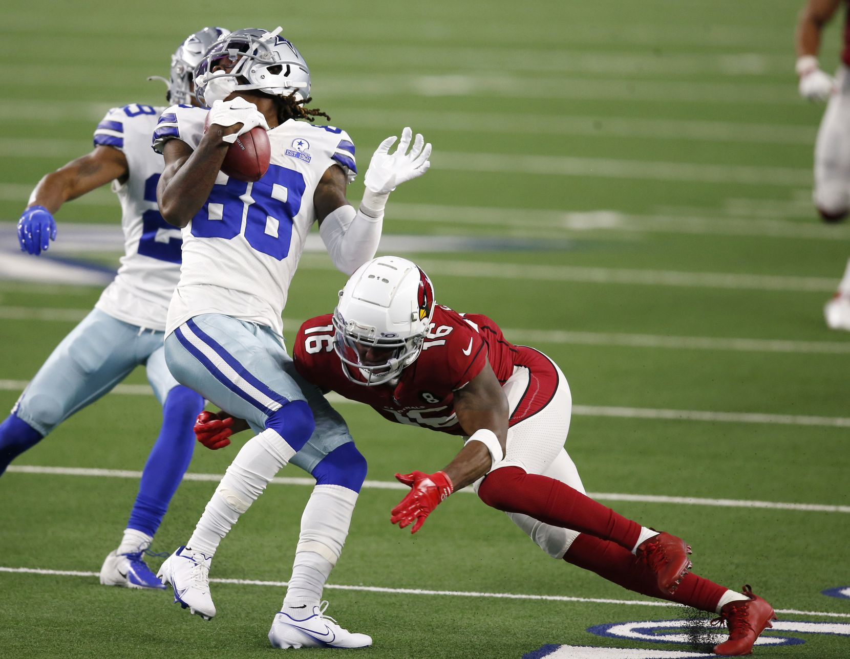 Dallas Cowboys wide receiver CeeDee Lamb (88) is tackled by Arizona Cardinals wide receiver Trent Sherfield (16) on a punt return during the first quarter of play at AT&T Stadium on Monday, October 19, 2020 in Arlington, Texas. (Vernon Bryant/The Dallas Morning News)