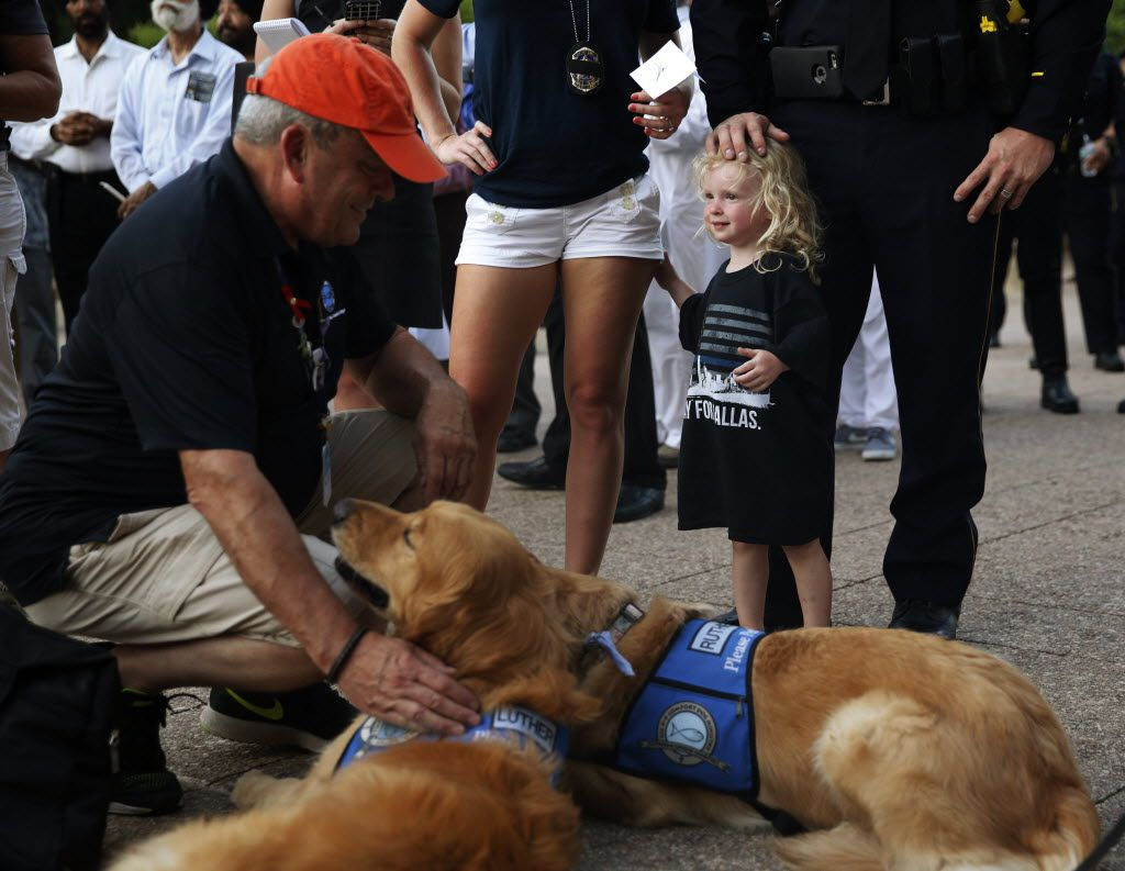 Senior Cpl. Daniel Sullivan (no face) with his daughter Sofia, 2 and wife Brandi, watch as Tim Hetzner president  Lutheran Christian Church offers his dogs to be pet during a candlelight vigil hosted by the Dallas Police Association at Dallas City hall in Dallas, TX July 11, 2016. (Nathan Hunsinger/The Dallas Morning News)