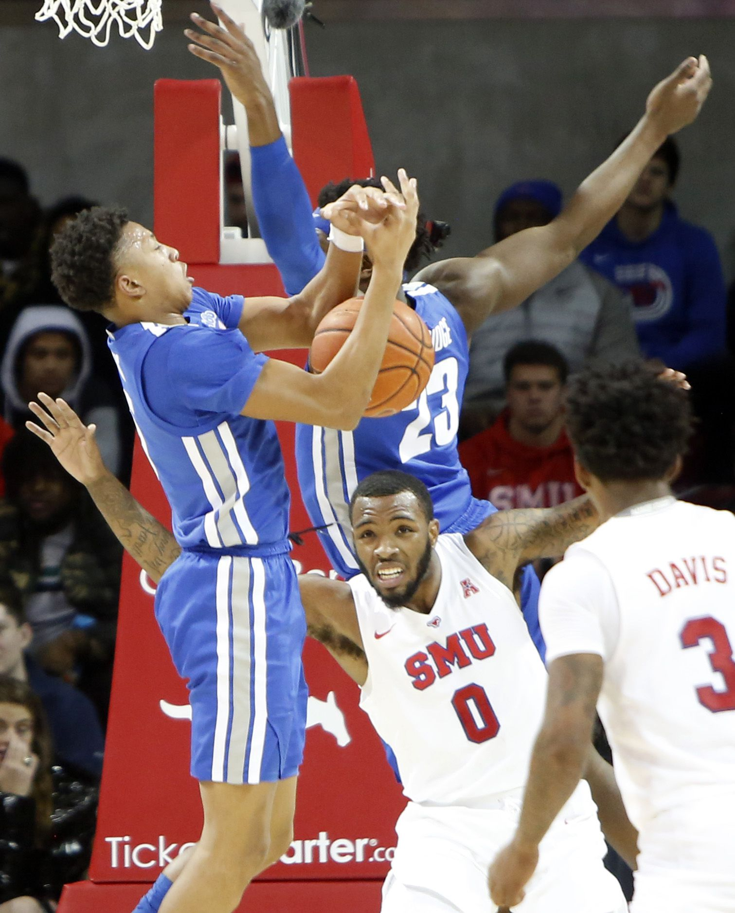 SMU guard Tyson Jolly (0) found himself in the middle of a battle for a rebound against Memphis guard Boogie Ellis (5) and center Malcolm Dandridge (23) during first half action. The two teams from the NCAA's American Athletic Conference played their men's basketball game at SMU's Moody Coliseum in Dallas on February 25, 2020.