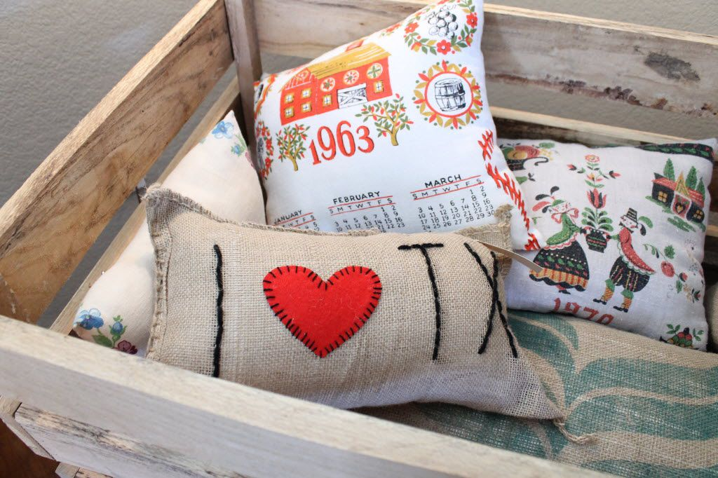 Among the handcrafted bath items at Denton's DIME store are home accessories, like these embroidered, handmade pillows.