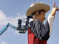 Los trabajadores sueltan las amarras utilizadas para levantar a Big Tex en el Big Tex Circle que da la bienvenida a los asistentes de la Feria Estatal que se inaugura el próximo viernes 24 de septiembre.