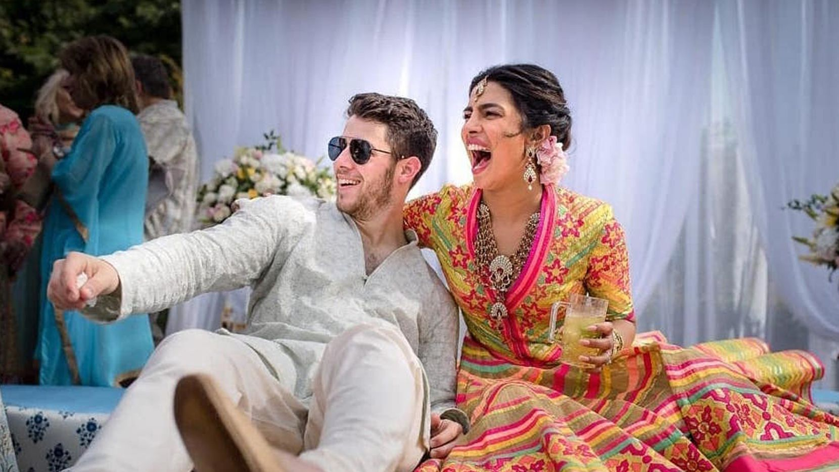 In this handout photo released by Raindrop Media, Bollywood actress Priyanka Chopra and Nick Jonas celebrate during a mehendi ceremony at Umaid Bhawan in Jodhpur, India.