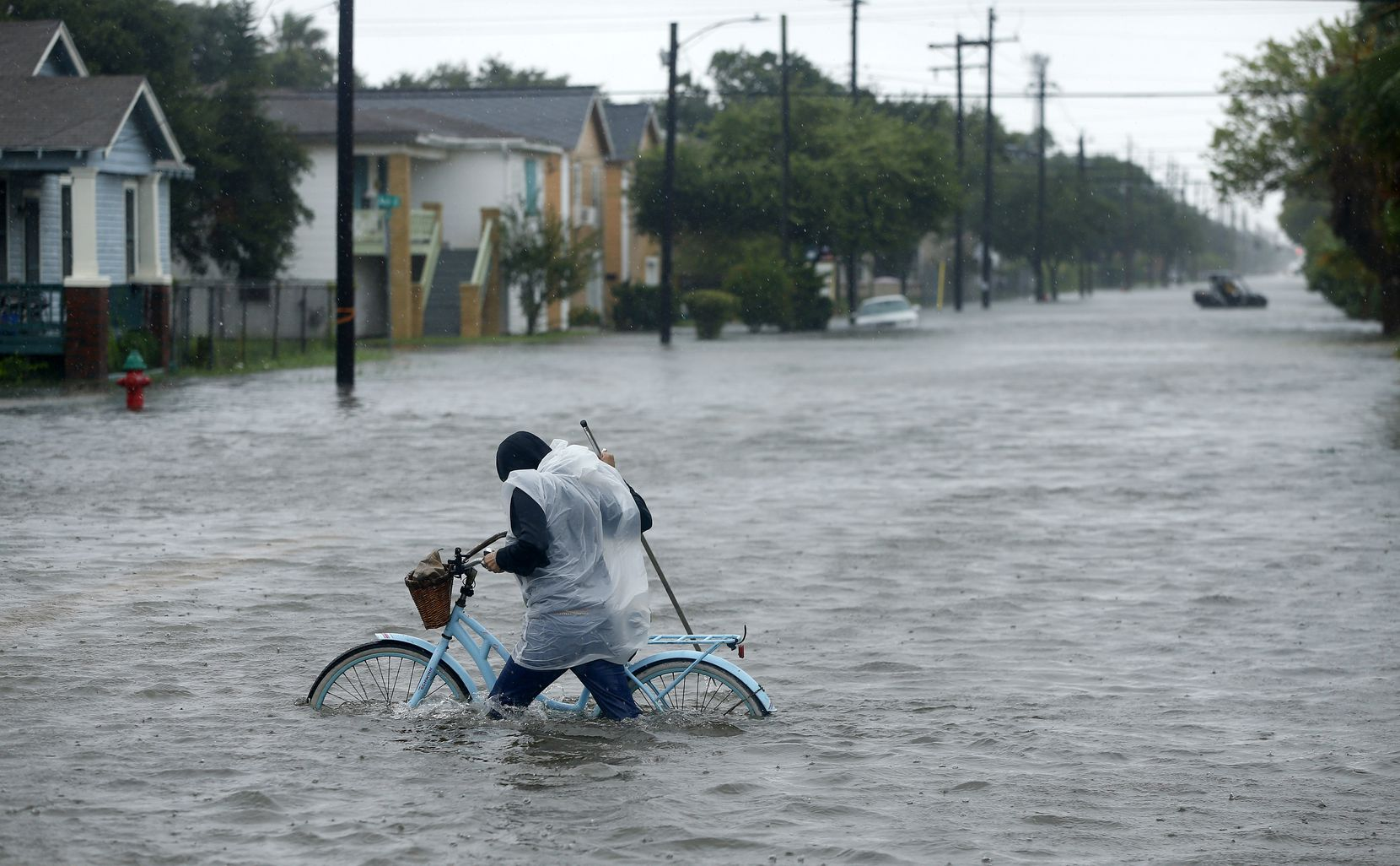 Monica Grant of Galveston pushes her bike through flooded streets near Broadway Ave.,Tuesday, August 29, 2017.