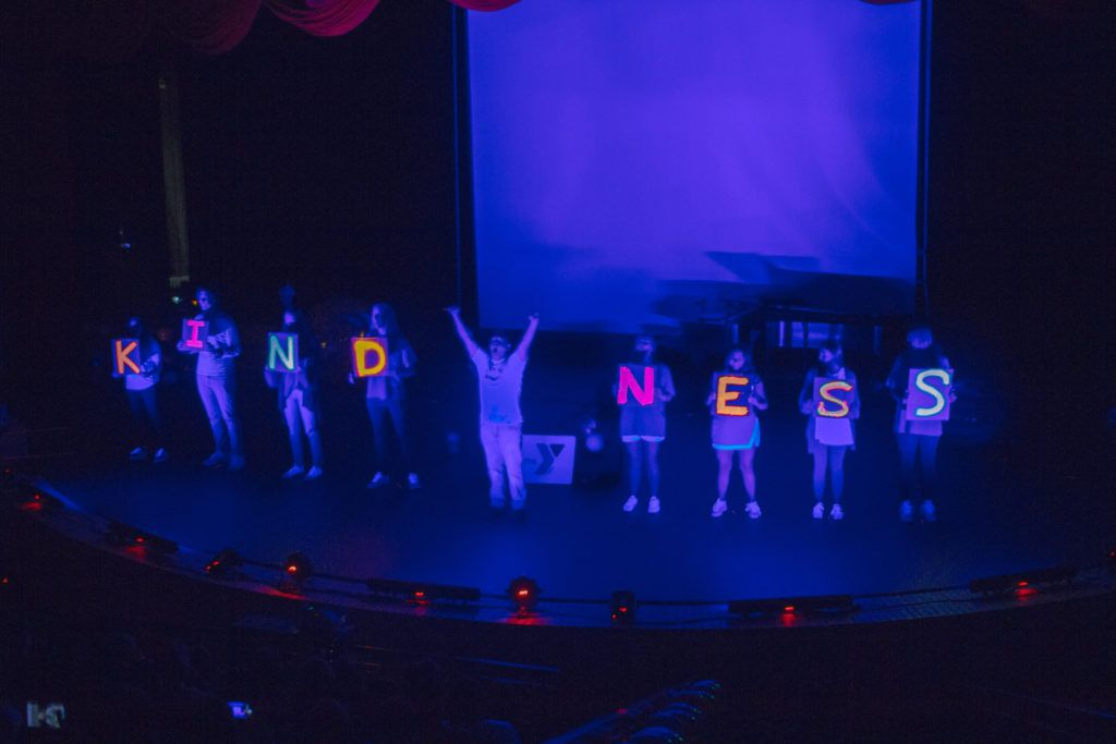 Kids demonstrate how kindness can be a light in the dark during a show by The Wezmore Project.