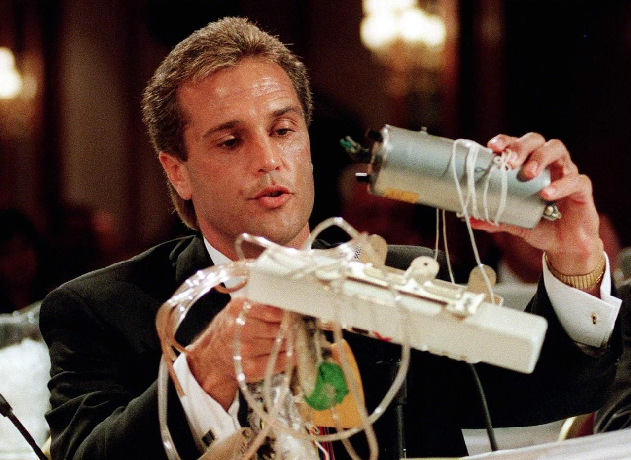 National Transportation Safety Board investigator Gregory Feith held up an oxygen generator as he testified at a 1997 hearing into the crash of a ValuJet Airlines jet the year before. The airliner went down in a Florida swamp after oxygen-generating canisters stored in the cargo hold overheated and fed a fire. All 110 aboard were killed.