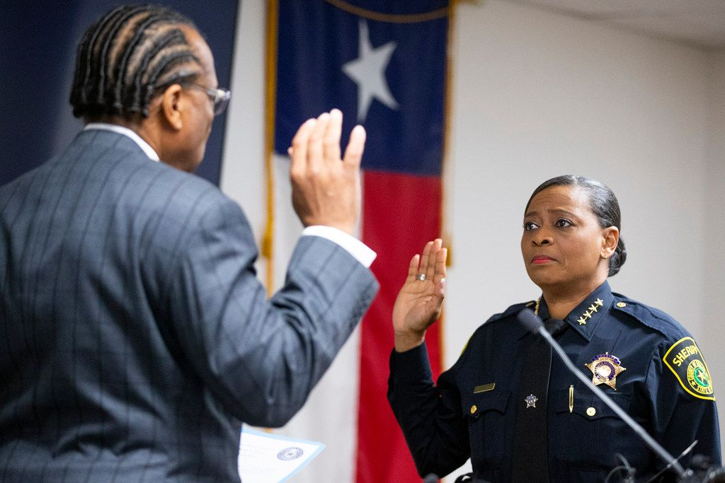 Commissioner John Wiley Price administers the oath of office to Sheriff Marian Brown on Tuesday.