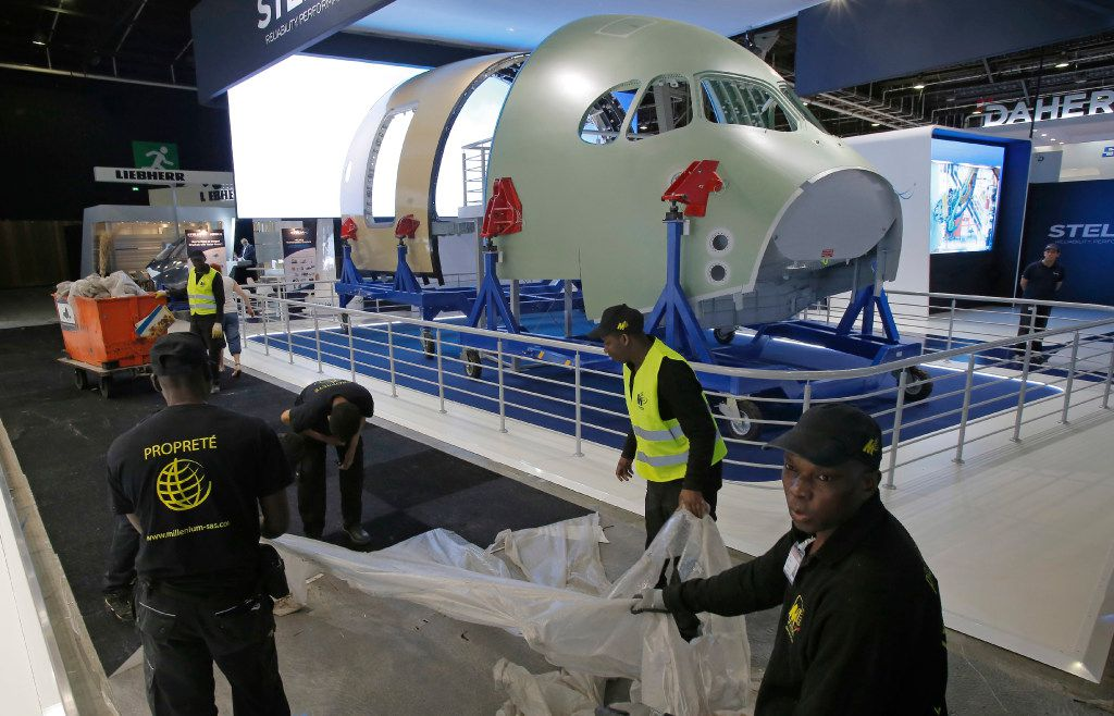 Employees take off a protection sheet at Paris Air Show, on the eve of its opening, in Le Bourget, east of Paris, France, Sunday, June 18, 2017.  (AP Photo/Michel Euler)