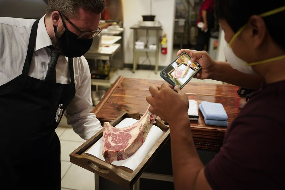 Mike Chen records a video as Luke Smithson presents his cut of steak at BAR-Ranch Steak Company on Wednesday, April 21, 2021, in Plano.