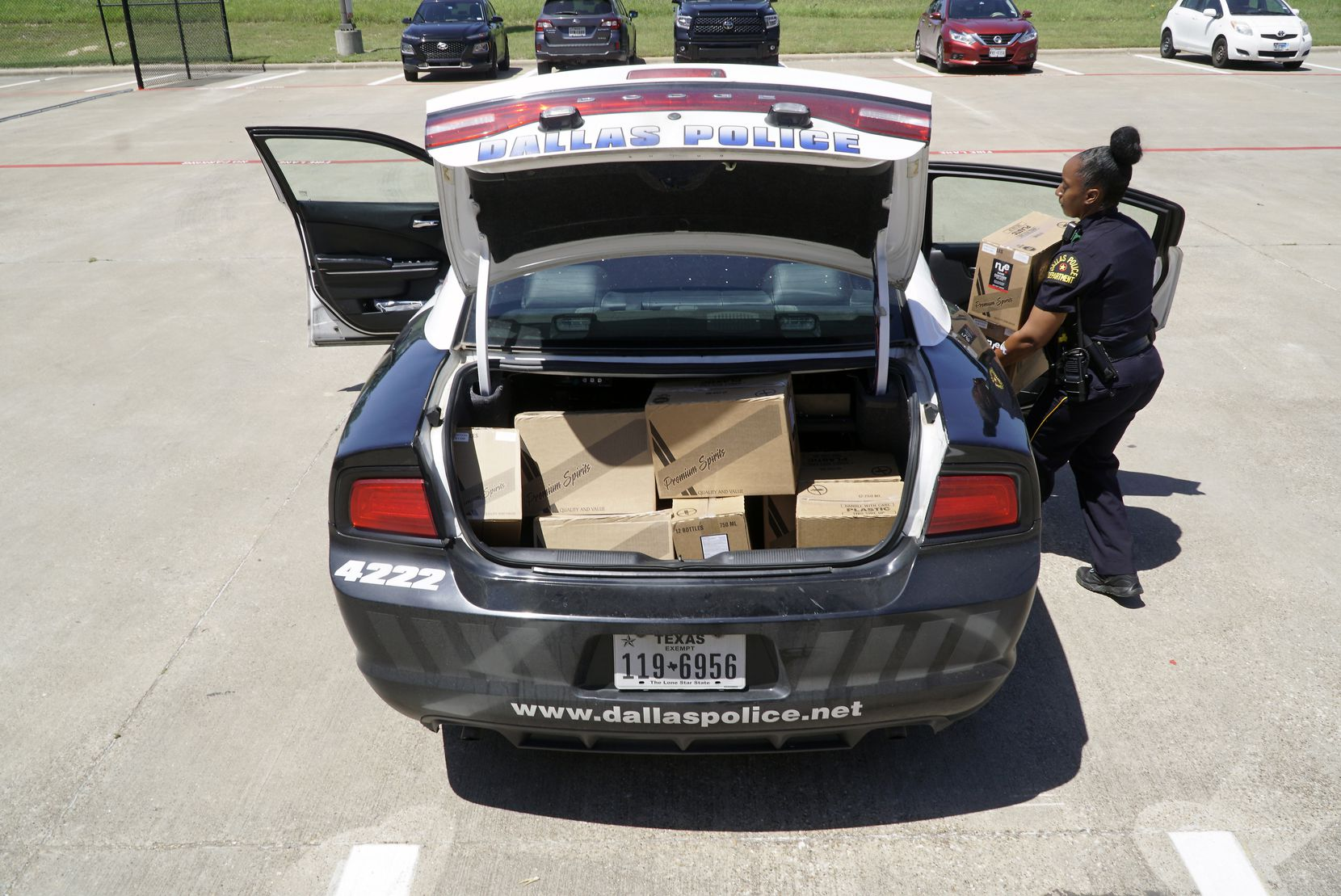 Dallas Police Officer Natasha Meadors loads boxes of hand sanitizer into her patrol car at the Dallas County Warehouse on Thursday.