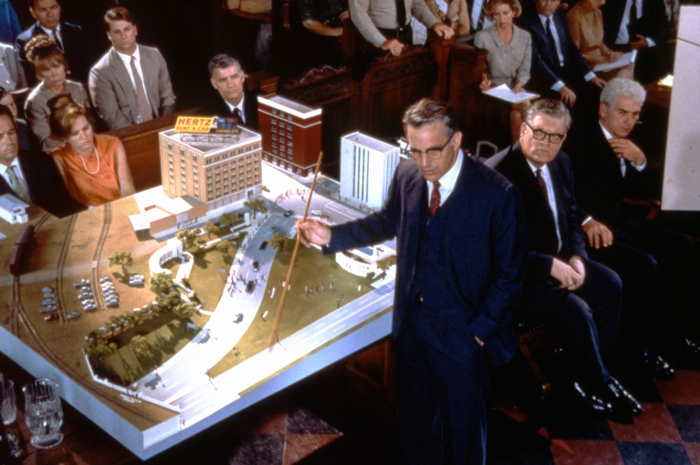 """This image from Oliver Stone's 1991 movie JFK shows Kevin Costner as New Orleans District Attorney Jim Garrison demonstrating the """"magic bullet"""" theory. Critics say Stone's film did more than anything to shape the public's perception of President John F. Kennedy's assassination. """"He made this kind of paranoid conspiracy theory respectable,"""" says New York writer Arthur Goldwag, author of Cults, Conspiracies, and Secret Societies."""