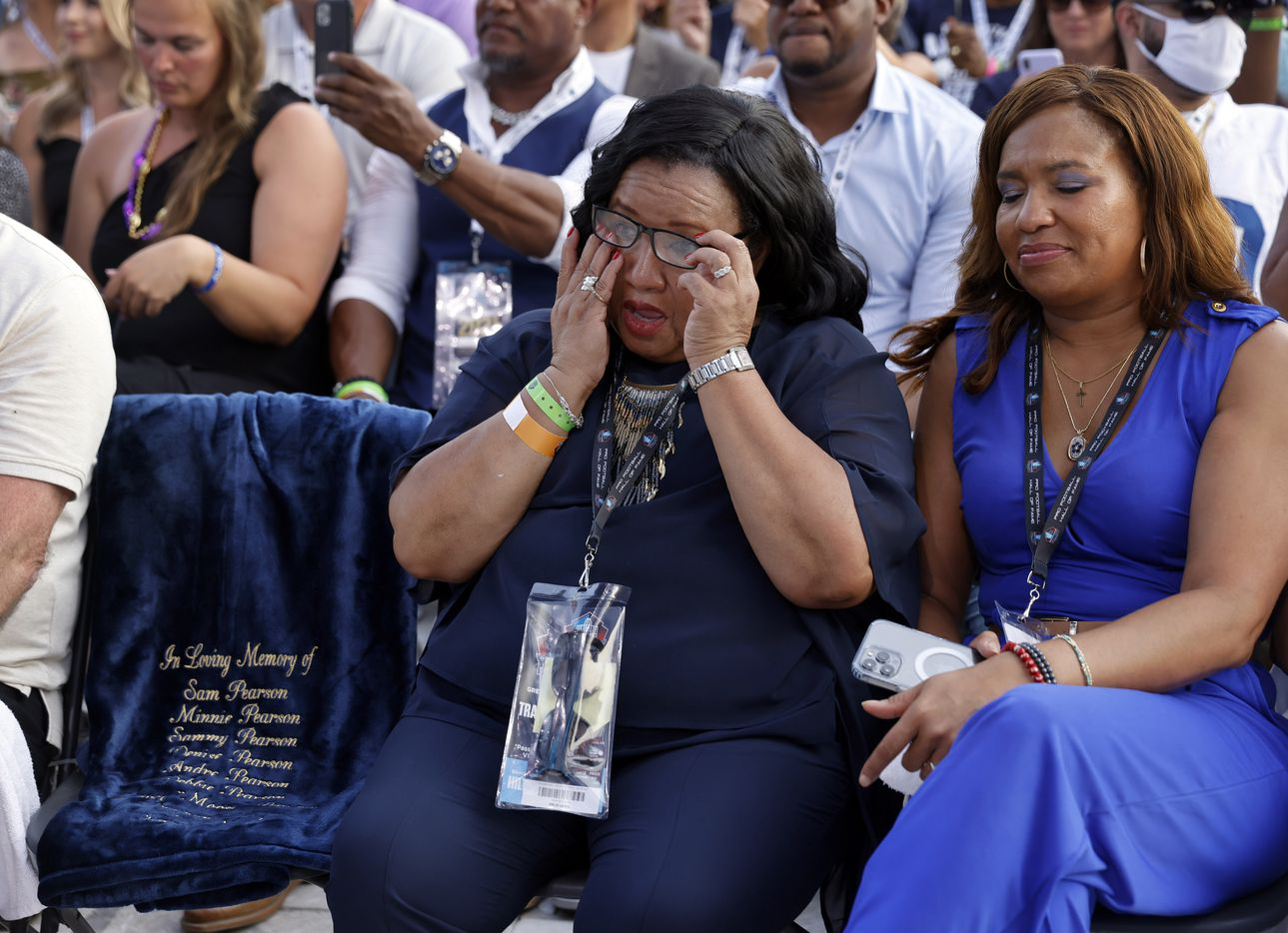 Sandra Pearson Hill (left), sister of Pro Football Hall of Fame inductee Drew Pearson of the Dallas Cowboys, wipes away tears next to an empty chair bearing the names of their parents, family members and friends who have passed away. Her oldest daughter Tori Nichole Pearson joined her as Drew acknowledged them in his acceptance speech during the Class of 2021 enshrinement ceremony at Tom Benson Hall of Fame Stadium in Canton, Ohio, Sunday, August 8, 2021. (Tom Fox/The Dallas Morning News)