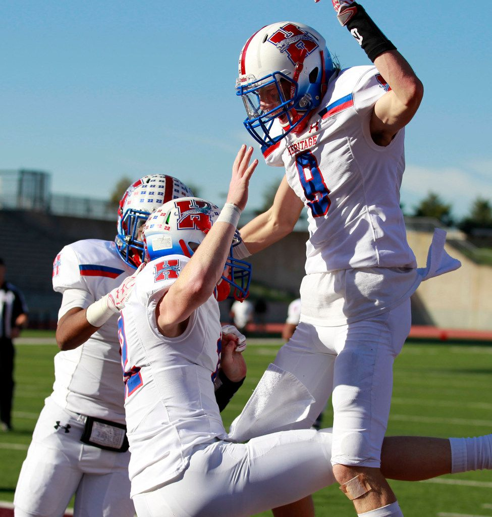 Midlothian Heritage QB Landon Ledbetter (12) and Jay Wilkerson (8) celebrate after a touchdown during the Class 4A  Division I area-round playoff high school football playoff game against Midlothian Heritage at Kincaide Stadium in Dallas, Friday, November 24, 2017. (John F. Rhodes / Special Contributor)