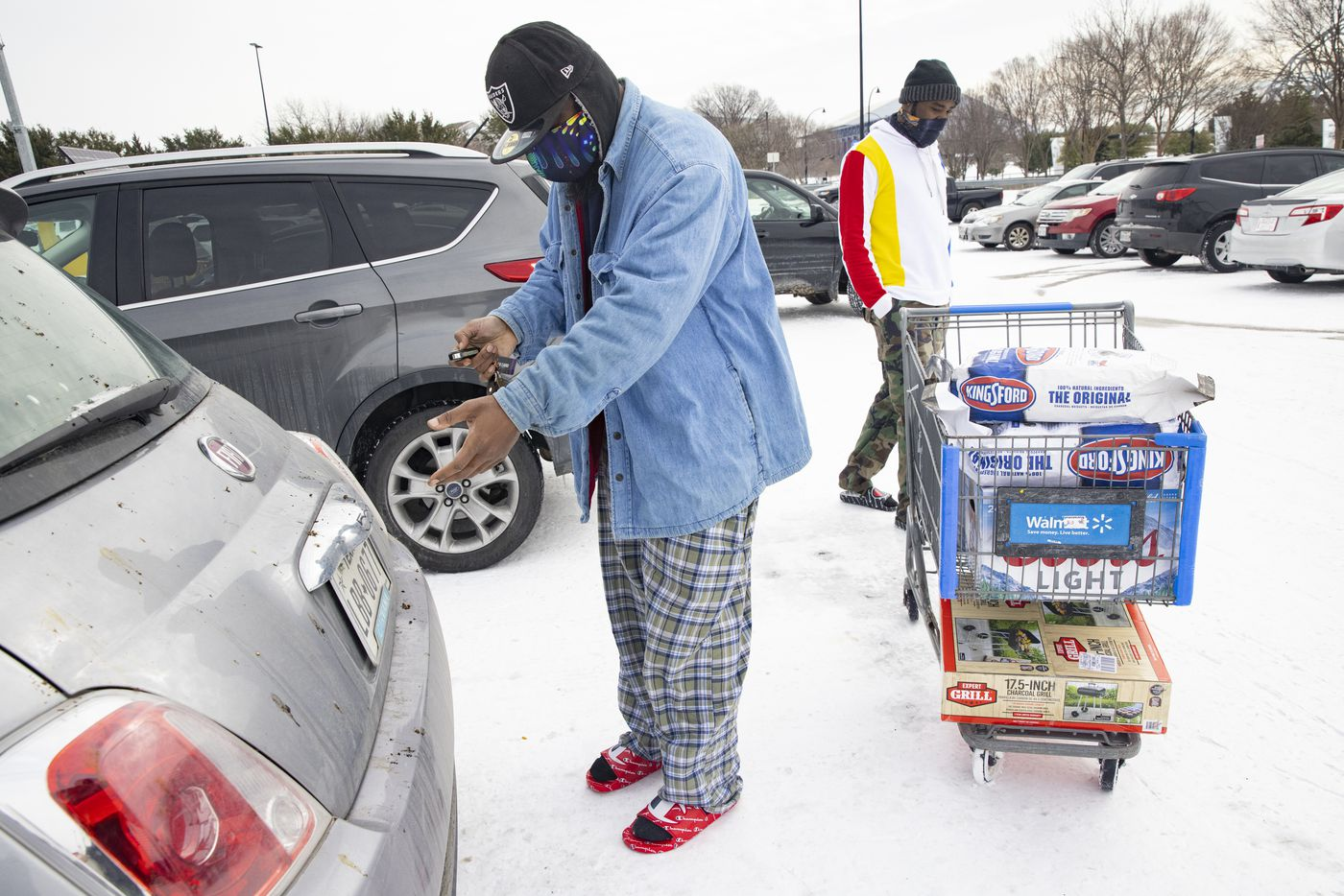 Reuben Brown (left) and Dekaetron McCalley wheel charcoal and a grill they bought at Walmart to their car at Walmart in Arlington on Tuesday, Feb. 16, 2021. They lost power yesterday and plan to use the charcoal and grill to cook food. (Juan Figueroa/ The Dallas Morning News)