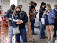 People wearing masks wait in line outside the Texas Department of Public Safety Driver License Office in Garland.