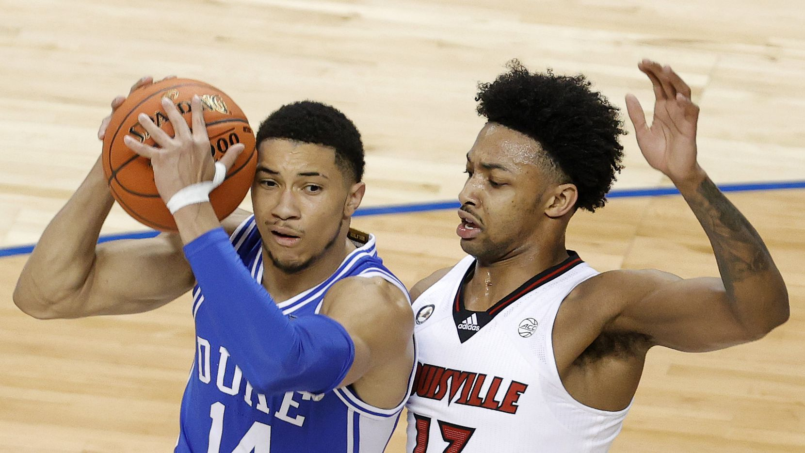 GREENSBORO, NORTH CAROLINA - MARCH 10: Jordan Goldwire #14 of the Duke Blue Devils drives against David Johnson #13 of the Louisville Cardinals during the first half of their second round game in the ACC Men's Basketball Tournament at Greensboro Coliseum on March 10, 2021 in Greensboro, North Carolina. (Photo by Jared C. Tilton/Getty Images)