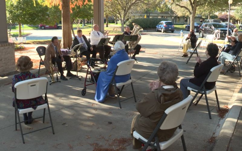 Members of the Texas Winds musical outreach are shown entertaining elderly Richardson residents, to help build morale during the COVID-19 pandemic.