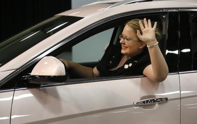 Beauty consultant Kei Denevan of San Antonio waves for a photo in the Mary Kay Cadillac at this year's convention.
