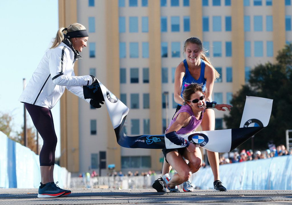 Shalane Flanagan, four-time Olympian, (left) watches as BMW Dallas Marathon winner Chandler Self  is helped by relay runner Ariana Luterman, 17, from Greenhill School, at the finish line Sunday in downtown.