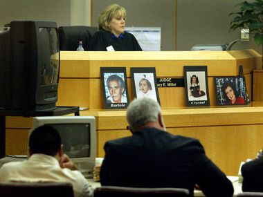 Abel Ochoa (bottom left) and Judge Mary Miller listened to the opening statements from prosecutors in Ochoa's capital murder trial in April 2003. On the ledge before the judge are photographs of family members who Ochoa killed.