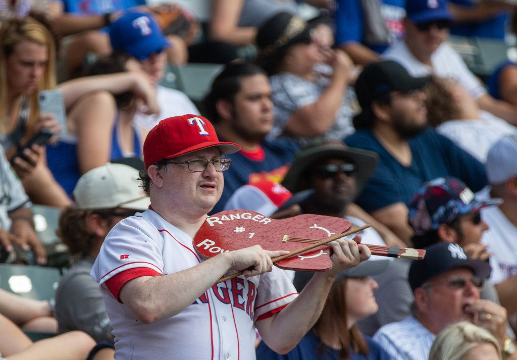 "A fan plays a makeshift violin while singing along with ""Deep in the Heart of Texas"" during the Texas Rangers' final game ever played at Globe Life Park in Arlington, Texas, on Sunday, Sep. 29, 2019. Following the game, fans enjoyed a ceremony and parade to place home plate at the new, adjacent Globe Life Field."