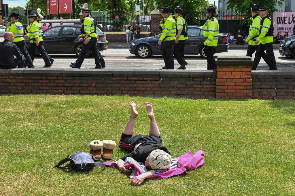 A woman sunbathes as police officers patrol around Old Trafford Cricket Ground ahead of the One Love Manchester tribute concert in Manchester on June 4, 2017.