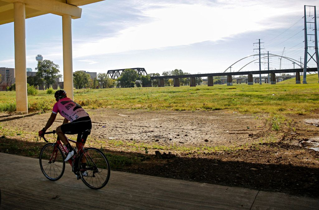 A biker rides along a trail underneath the Margaret Hunt Hill Bridge Monday, October 31, 2016 in Dallas. Mayor Mike Rawlings announced Monday the donation of $50 million to help fund a park in the area. (G.J. McCarthy/The Dallas Morning News)
