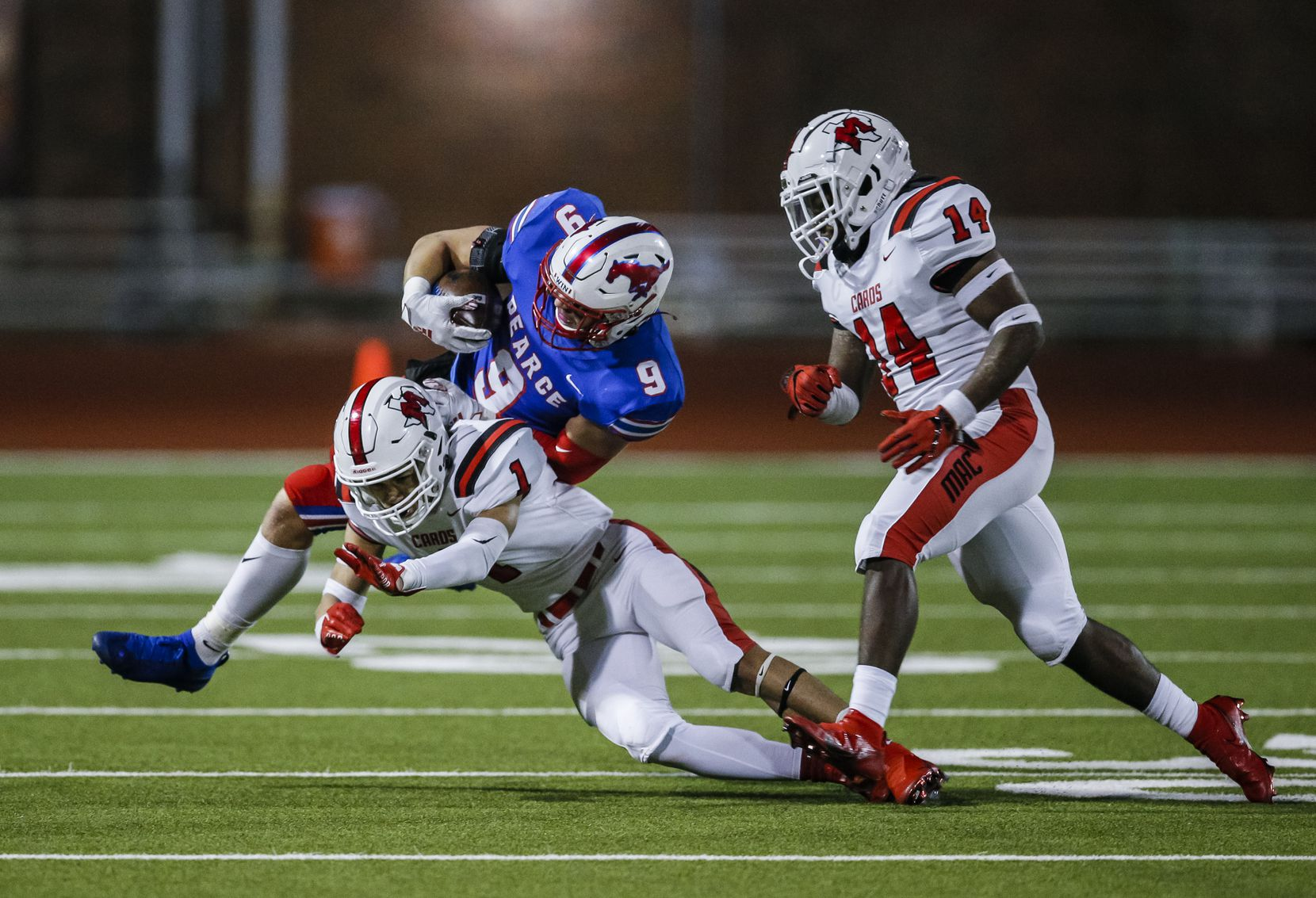 Irving MacArthur seniors Roland Jackson (1) and Chandler Neal (14) tackle JJ Pearce senior halfback Dylan Adams (9) during the first half of a high school playoff football game at Eagle-Mustang Stadium in Richardson, Thursday, December 3, 2020. (Brandon Wade/Special Contributor)