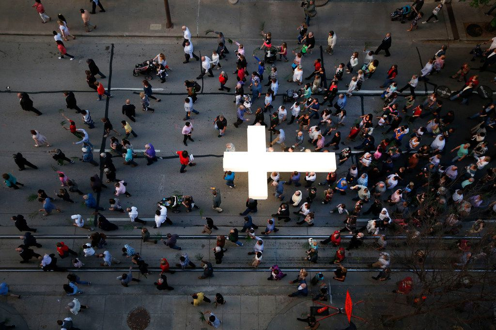 Church members carry an illuminated cross during the March for Eternal Life led by members of First Baptist Dallas in downtown Dallas on Palm Sunday, March 25, 2018. The march comes a day after the March for Our Lives protest for stricter gun control. (Rose Baca/The Dallas Morning News)