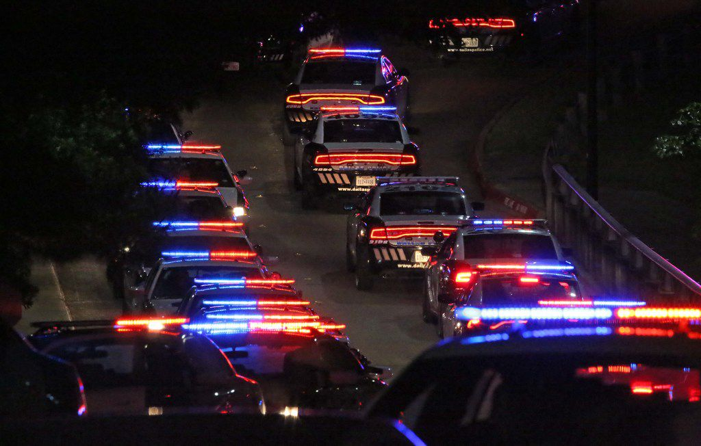 Dallas police cars line up to be in the motorcade as the body of slain officer Rogelio Santander Jr. is transported to the medical examiner from Presbyterian Hospital in Dallas in the early morning hours on Friday.