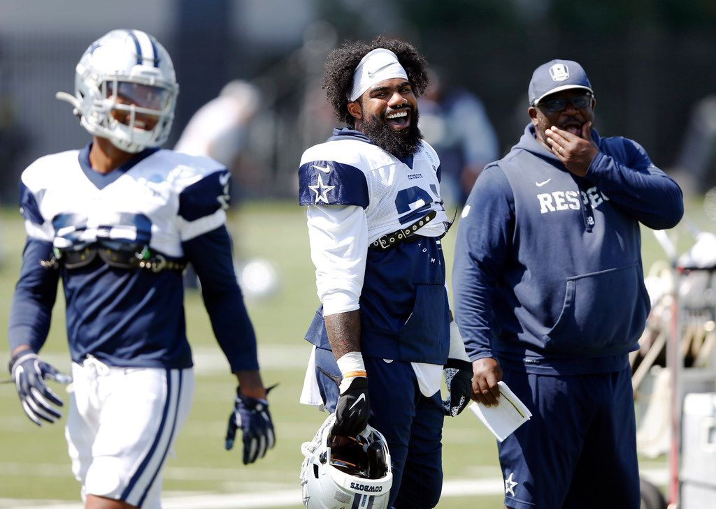 Dallas Cowboys running back Ezekiel Elliott (21) and Dallas Cowboys running backs coach Gary Brown laugh with Dallas Cowboys running back Tony Pollard (20) as he passes by during practice at The Star in Frisco, Texas on Wednesday, September 4, 2019.