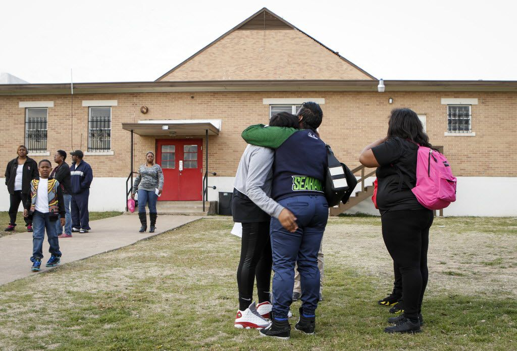 Parent Catrina Henderson (center, in blue shirt), comforts a distraught student at the school's Dallas campus after the closing was announced. (Jim Tuttle/The Dallas Morning News)
