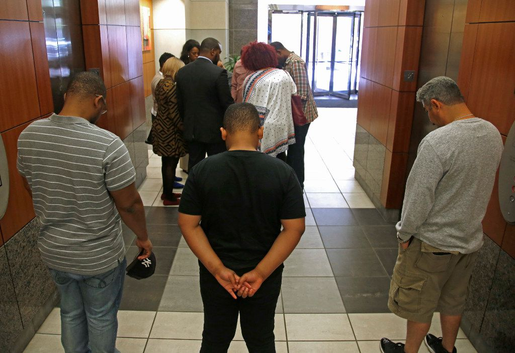Charmaine (not visible) and Odell Edwards (far right in plaid shirt), parents of Jordan Edwards, stand in a prayer circle with their attorney, Lee Merritt (black suit), and family and friends after a press conference about the Balch Springs police shooting death of their son, in the lobby of Merritt's law office building in Dallas Monday, May 1, 2017.