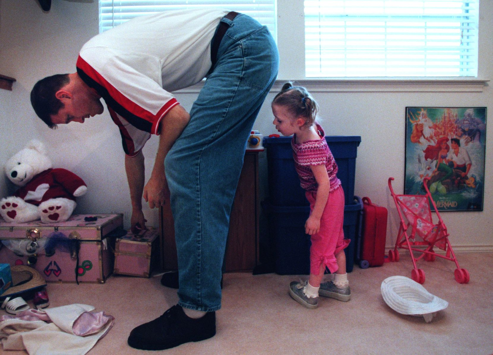 Dallas Mavericks center Shawn Bradley helps his daughter Chelsea, 3, find a toy in the upstairs play room at their Plano home.
