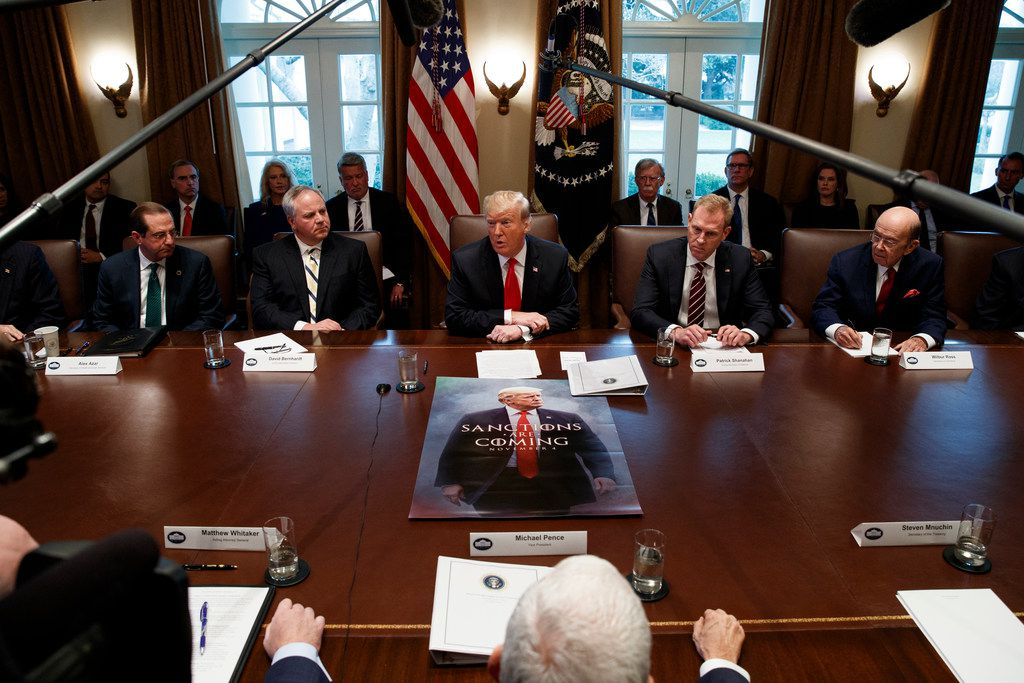 """President Donald Trump speaks Wednesdayduring a cabinet meeting at the White House.. From left are Secretary of Health and Human Services Alex Azar, acting Secretary of the Interior David Bernhardt, Trump, acting Secretary of Defense Patrick Shanahan, and Secretary of Commerce Wilbur Ross. On the table: a movie-style poster of Trump that says """"Sanctions are Coming."""""""