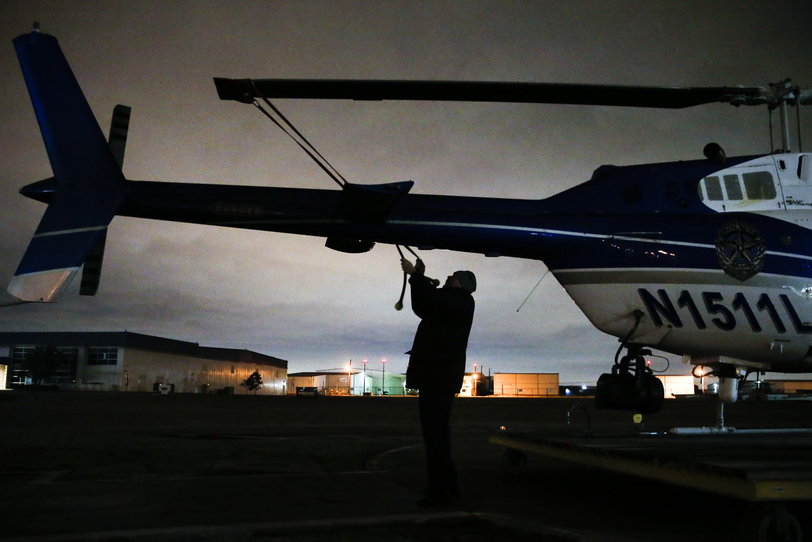 Senior Cpl. Mark Colborn ties down the main rotor blade of one of the unit's helicopters outside a hangar at Dallas Executive Airport as high winds blow into Dallas.