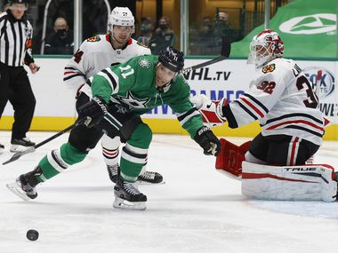 Dallas Stars center Andrew Cogliano (11) reaches for the puck in front of Chicago Blackhawks goaltender Kevin Lankinen (32) during the third period of play at American Airlines Center on Tuesday, February 9, 2021 in Dallas.