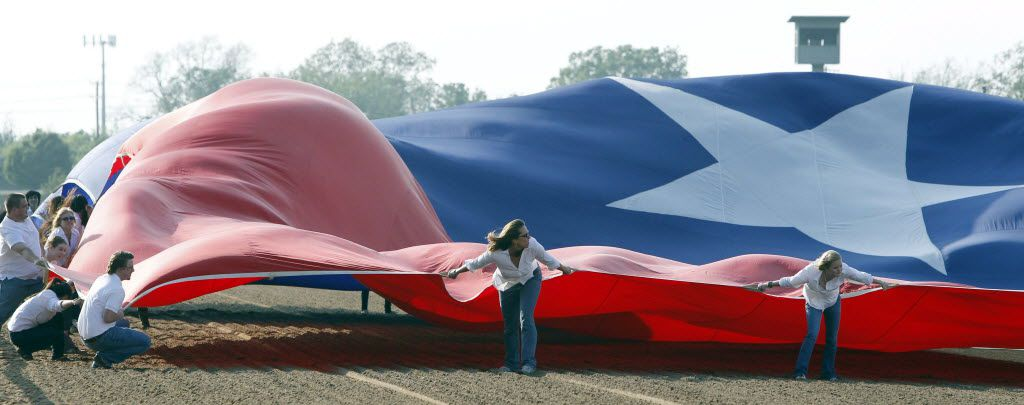 A flag crew tries to control a giant Texas flag in windy conditions during opening day of the 2011 Spring Thoroughbred Season at Lone Star Park at Grand Prairie on April 14, 2010.