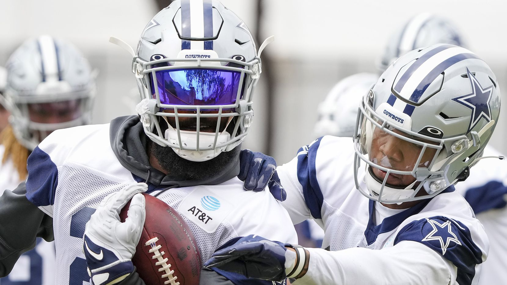 Dallas Cowboys running back Ezekiel Elliott (21) works against  running back Tony Pollard (20) in a fumble drill during a practice at training camp on Tuesday, July 27, 2021, in Oxnard, Calif.