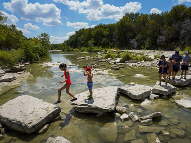Park visitors cross the Paluxy River at Dinosaur Valley State Park in Glen Rose, one of several nearby spots perfect for a spring break day trip.