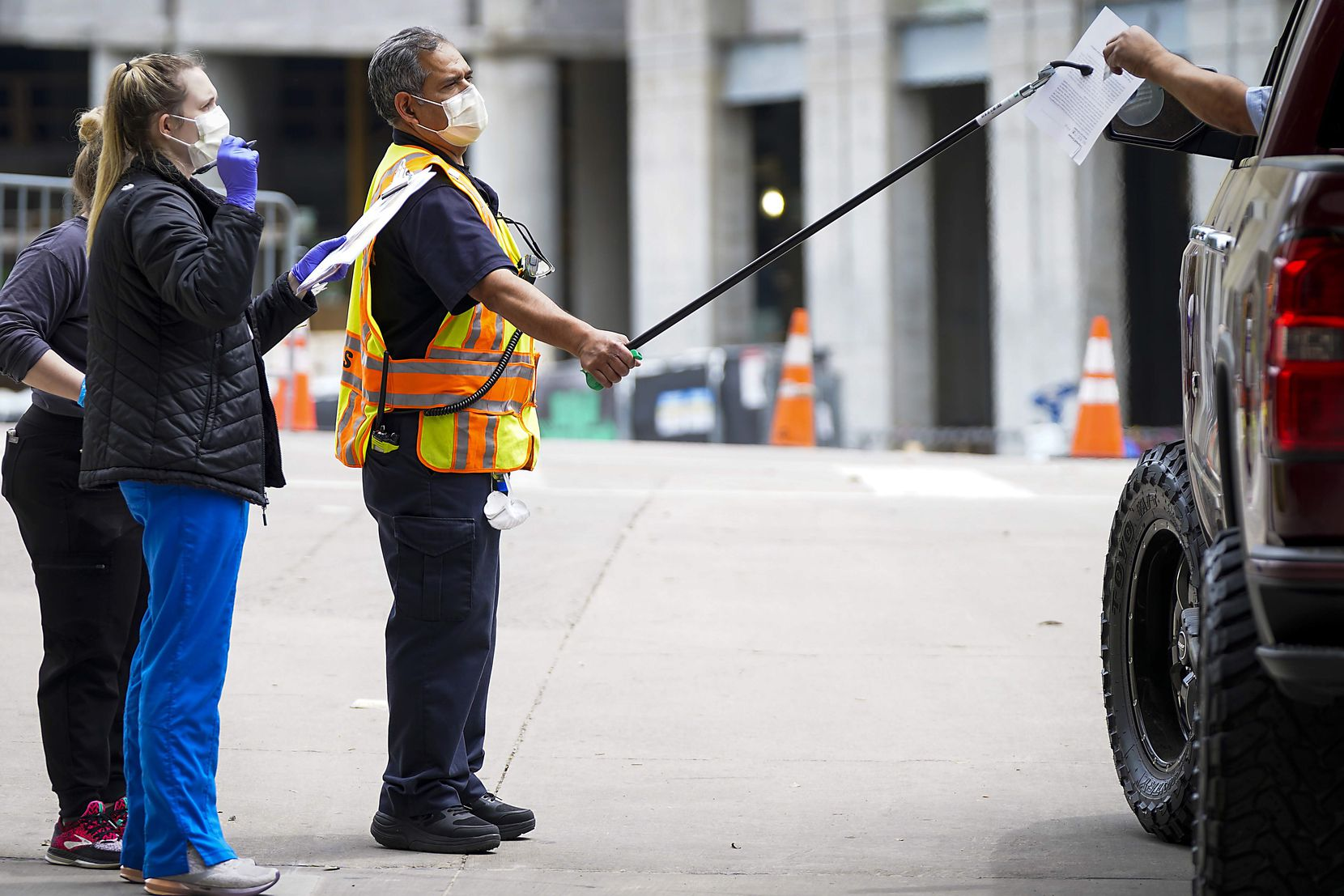 Health-care workers used a gripper tool to give paperwork to a person being screened at a COVID-19 drive-through testing site at American Airlines Center in April.