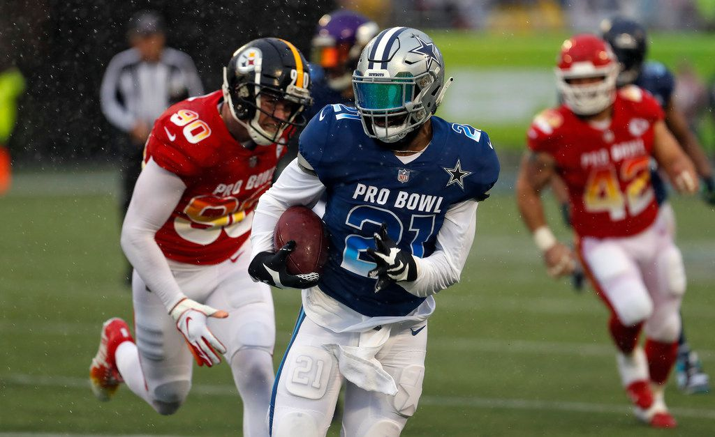 NFC running back Ezekiel Elliott (22), of the Dallas Cowboys, gets away from AFC linebacker T.J. Watt (90), of the Pittsburgh Steelers, during the second half of the NFL Pro Bowl football game Sunday, Jan. 27, 2019, in Orlando, Fla. (AP Photo/Mark LoMoglio)