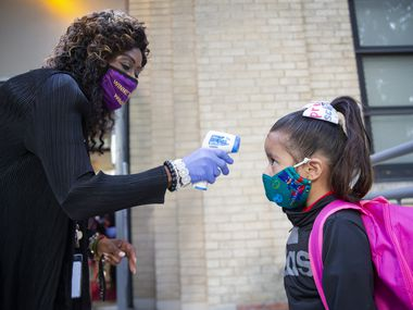 """Assistant principal Clara Daniels takes Riley Pereyda, 4, temperature before her in-person classes during the students' second """"first day of school"""" at Winnetka Elementary School in Dallas Sept. 28, 2020. (Juan Figueroa/ The Dallas Morning News)"""