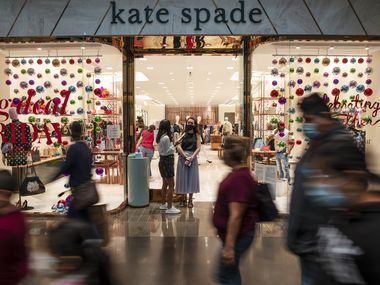 Sales associate Desiree Leija, left, and store leader Ashley McGill, right, wait outside the store front of Kate Spade for shoppers at NorthPark Center in Dallas.