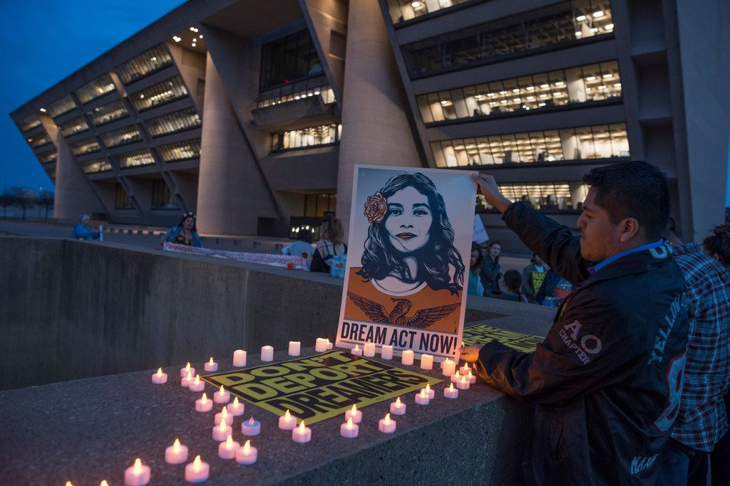 Luis Gonzalez, a DACA recipient originally from Mexico, places candles around a protest sign before a vigil at Dallas City Hall on March 5, 2018.